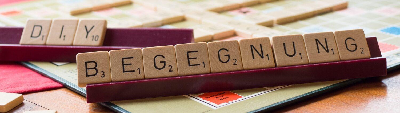 Die Wörter DIY für Selbermachen und Begegnung zusammengelegt aus kleinen Holzplättchen mit Buchstaben wie in dem Kreuzworträtselspiel