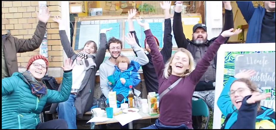 Menschen vor der Magdelstube mit Händen in die Höhe, jubelnd und sich freuen über das gemeinsame Projekt Magdelstube