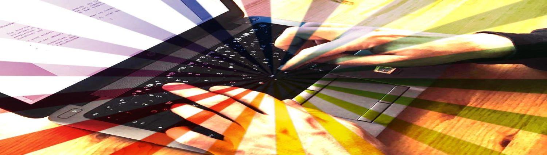 Tippende Finger vor einer Tastatur mit Regenbogenfarben